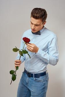 Романтичный мужчина с красной розой и в голубой рубашке с галстуком-бабочкой на шее на сером фоне.