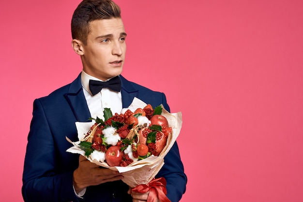 Romantic man with bouquet of flowers and in bow tie on pink background cropped view.