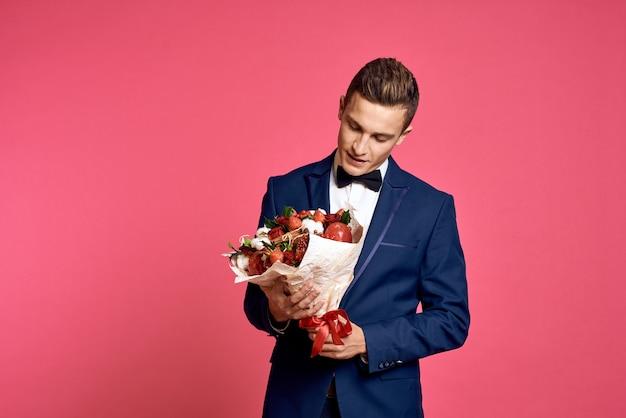 Романтический мужчина с букетом цветов и в галстуке-бабочке на розовом фоне обрезанный вид