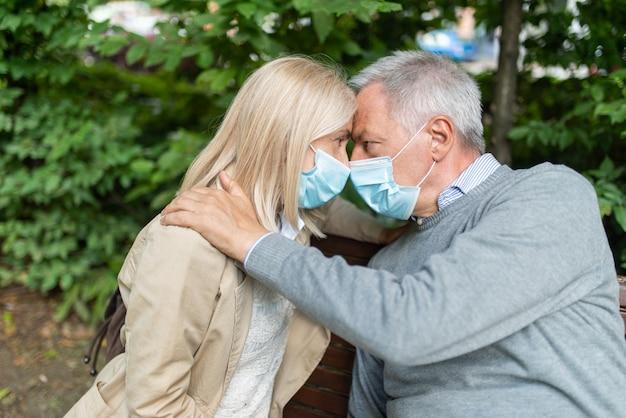 コロナウイルスのパンデミック中に公園でロマンチックな成熟したカップル