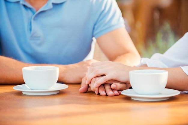 ロマンチックな瞬間。テーブルの上にコーヒーカップと一緒に歩道のカフェで一緒に座っている間手をつないでいるカップルのクローズアップ