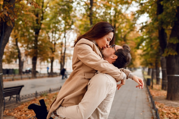 Romantic moments. happy beautiful couple in love fooling around and having fun in amazing autumn park.