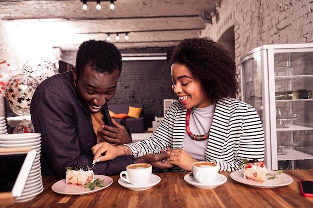 Романтические моменты. радостная счастливая пара ест торт, прекрасно проводя время вместе