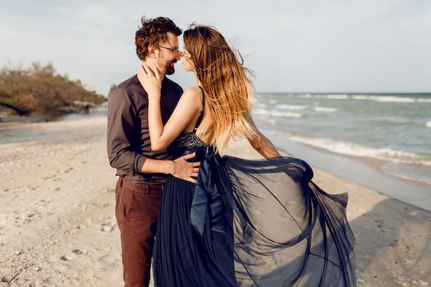 美しいカップル、ファッショナブルな女性、海の近くに屋外ポーズの男のロマンチックな瞬間。素晴らしい青いドレスとカジュアルな服装。新婚旅行の休暇。