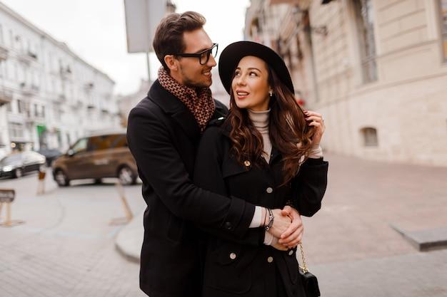街を歩いて、抱き合って一緒に時間を楽しんでいる愛の美しいエレガントなカップルのロマンチックな瞬間。温かみのある色。バレンタイン