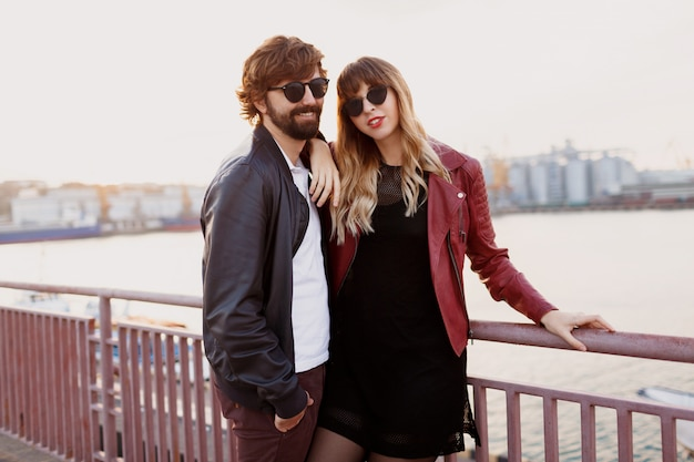 スタイリッシュなカップルが恋に落ちたり、会話をしたり、時間を楽しんだりするロマンチックな瞬間。橋の上を歩く妻とハンサムな男。