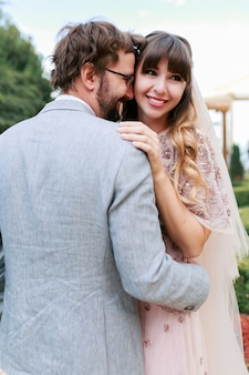 Романтические моменты свадебной пары. жених и невеста обнимаются и веселятся вместе.