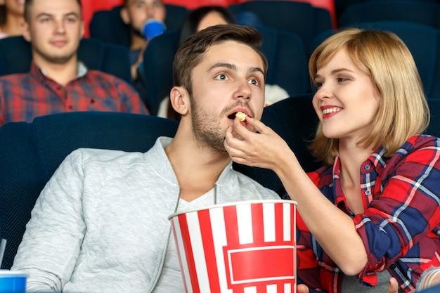 ロマンチックな気分。映画館でポップコーンを共有する美しく、幸せな若いカップルの水平方向の肖像画