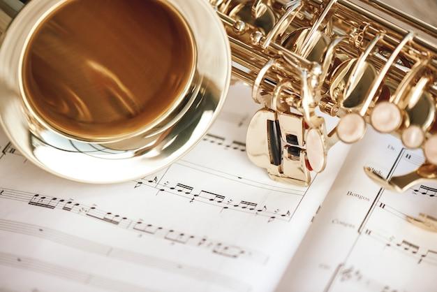 Романтическое утро. крупным планом вид саксофона и чашки кофе, лежащих на музыкальных нотах. музыкальные инструменты.