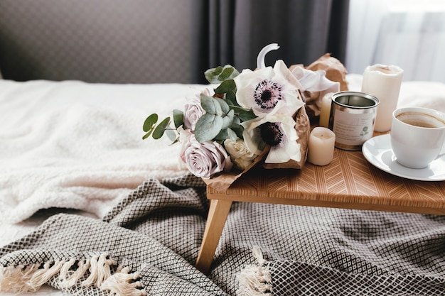 Romantic morning. wooden coffee table with flowers on bed with plaid, coffee cup, flowers and candles. lilac roses with eucalyptus and anemones. interior gray tones