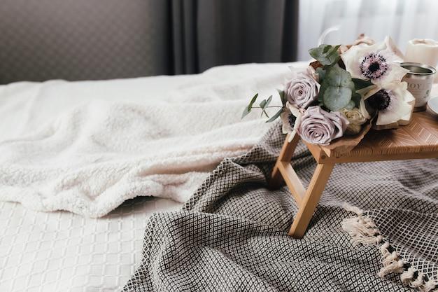ロマンチックな朝。格子縞、コーヒーカップ、花、キャンドルとベッドの上に花と木製のコーヒーテーブル。ユーカリとイソギンチャクのライラックバラ。インテリアグレートーン。