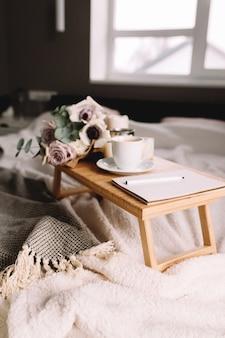 Романтическое утро. деревянный журнальный столик с цветами на кровати с пледом, чашка кофе, цветы и свечи, блокнот, ручка. сиреневые розы с эвкалиптом и анемонами. интерьер в серых тонах.
