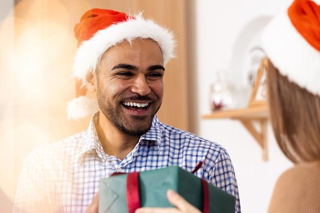 Романтическая многонациональная пара в рождественских шляпах обменивается подарками