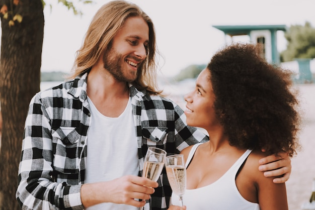 Romantic multiracial couple champagne on beach.