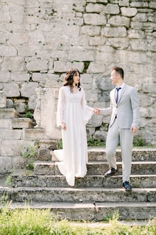 Romantic newlywed asian couple posing in the ruins of an old castle, holding hands and standing on the stone stairs