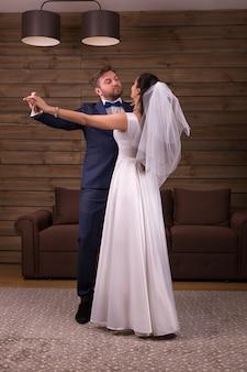 Романтическая пара молодоженов танцует свадебный танец на деревянной комнате