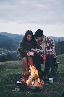 낭만적인 밤입니다. 산에서 모닥불 옆에서 워밍업하면서 뜨거운 음료를 즐기는 아름다운 젊은 부부