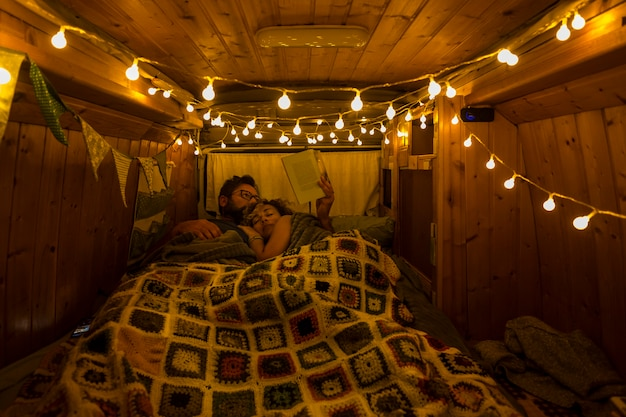 Romantic night inside an old restored wooden vintage van with adult people couple sleeping by night together in the tiny traveler house