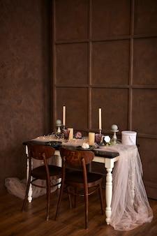 Сервировка романтического или свадебного ужина или сервировка праздничного стола, коричневые, розовые и золотые украшения со свечами и гирляндами.