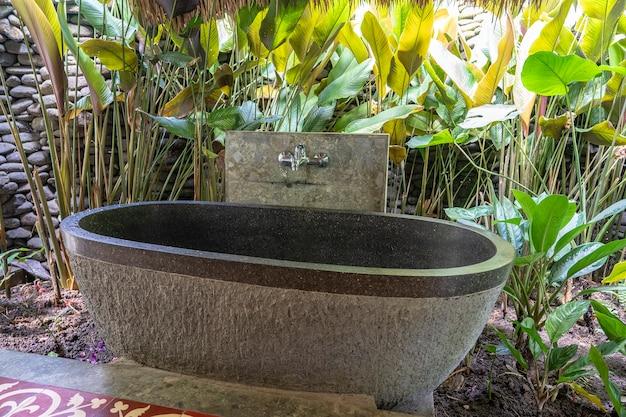 インドネシア、バリ島のトロピカルヤードにあるロマンチックな屋外石造りのバスルーム