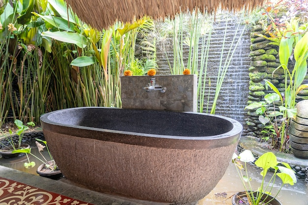 Романтическая каменная ванная комната на открытом воздухе в тропическом дворе на острове бали, индонезия