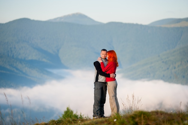 Romantic pair hugging against beautiful mountain landscape with morning haze over the mountains