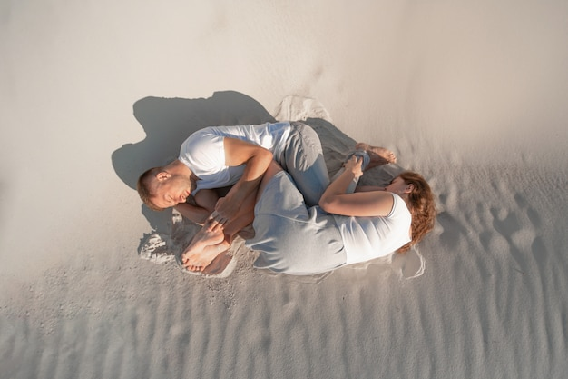Romantic pair laying on white sand