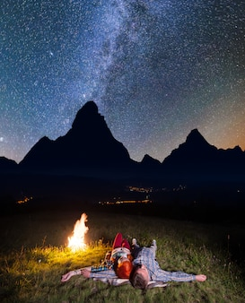 Romantic pair looking to the bright stars and lying near the bonfire.