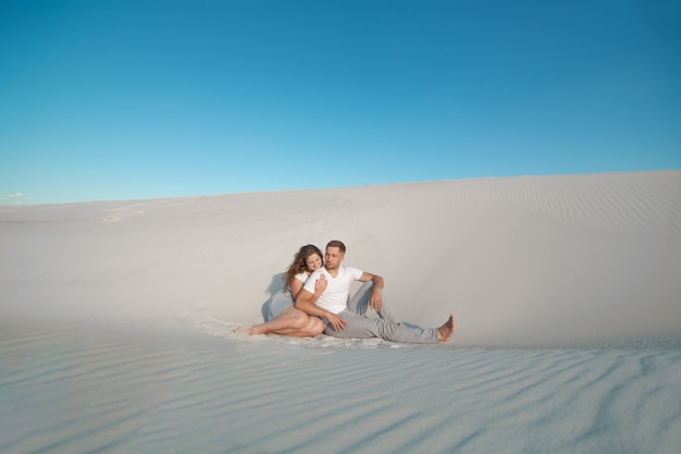 Romantic pair sit on white sand and huggins, in desert
