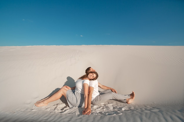 Romantic pair sit on white sand and huggins in desert