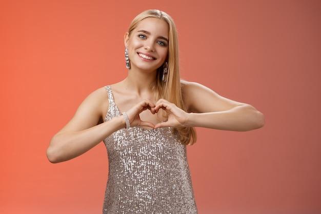 銀のドレスの華麗なロマンチックな情熱的な魅力的な素敵なブロンドの魅力の女性は、心の愛のジェスチャーが同情の情熱を表現し、喜んで笑顔、立っている赤い背景を崇拝する関係を示しています。