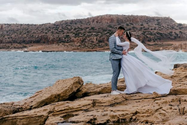 キプロスの海と岩の風景を背景に抱き合う新婚夫婦のロマンチックな写真
