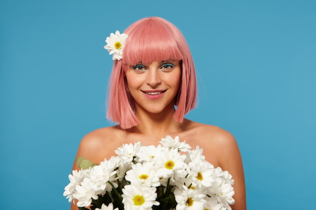 Romantic photo of young lovely pink haired woman with colored makeup holding huge bouquet of flowers and looking positively with charming smile, isolated
