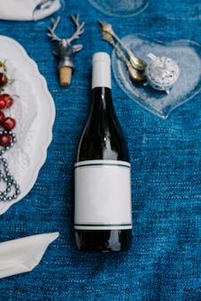 公園の芝生の上のロマンチックなピクニック、おいしい食べ物:バスケット、ワイン、ブドウ、桃、バゲット、カップケーキ、イチジク、チーズ、青いテーブルクロス、シャンパン付きの2つのワイングラス