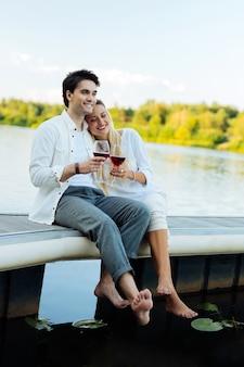 ロマンチックなピクニック。ピクニックをしながら川の近くに一緒に座って幸せな楽しい夫婦