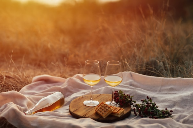 川と夕日のある山でのロマンチックなピクニック。ワイン、グラス、格子縞、デザートのボトル。