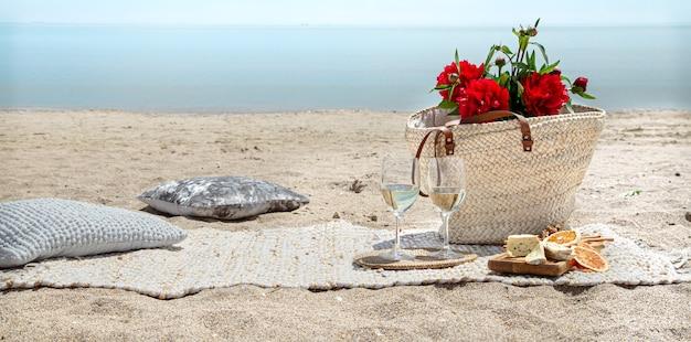 샴페인, 스낵 및 꽃과 함께 모래 해변에서 낭만적 인 피크닉. 휴가 및 로맨스 개념.