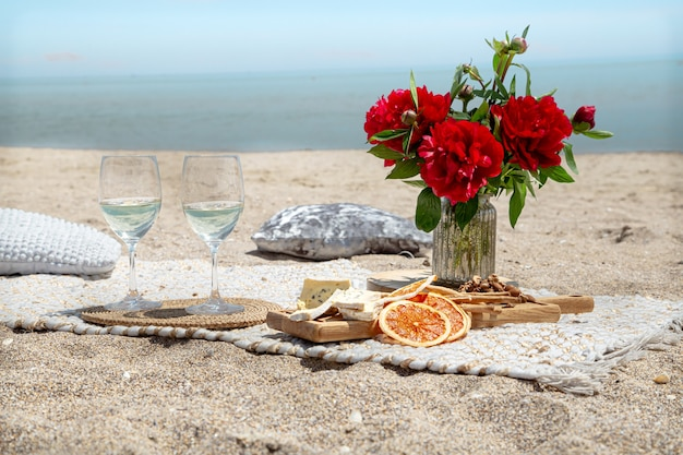 Romantic picnic on the sandy beach with champagne, snacks and flowers. vacation and romance concept.