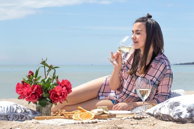 Un romantico picnic sulla riva sabbiosa della spiaggia con fiori e bicchieri di bevande. il concetto di vacanza estiva.