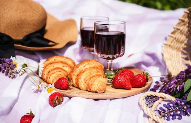 Романтический пикник в летний день. пикник с вином и фруктами на свежем воздухе на фоне зеленой травы.