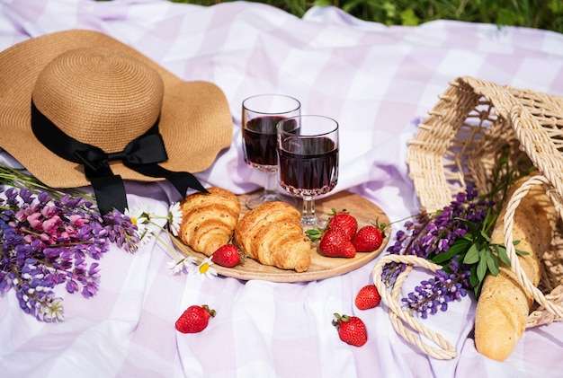 Romantic picnic scene on summer day. outdoor picnic with wine and a  fruit  in the open air on the background of green grass. Premium Photo
