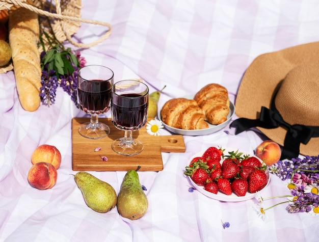 Romantic picnic scene on summer day. outdoor picnic with wine and a  fruit  in the open air on the background of green grass.