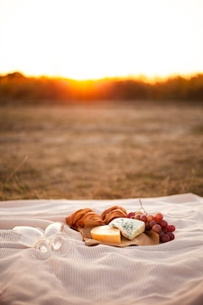 Romantic picnic for two on a sunset background.
