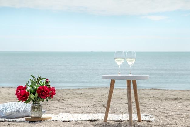 꽃과 바다로 샴페인 잔과 함께 낭만적 인 피크닉. 휴일의 개념.