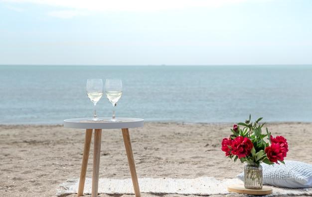 바다로 꽃과 샴페인 잔과 함께 낭만적 인 피크닉. 휴일의 개념.