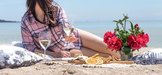 Un romantico picnic con fiori e bicchieri di bevande in riva al mare. vacanze estive e concetto di relax.