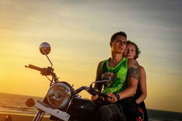 Romantic picture with a couple of beautiful stylish bikers at sunset. handsome guy with tatoo and young sexy woman enjoy themselves in motorbike trip