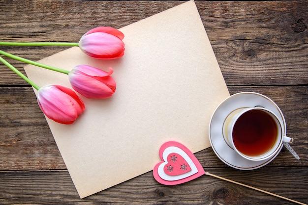 チューリップ、紅茶、木製のテーブルの上のノートとロマンチックな写真