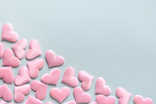 Romantic pink hearts on blue background, valentine's day greeting card.