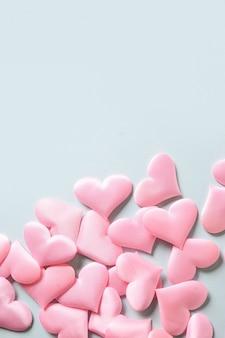 青い背景にロマンチックなピンクのハート。コピースペース付きのバレンタインデーのグリーティングカード。愛の概念。